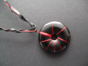 A round donut of obsidian stone wrapped in metallic red wire in a design similar to a firework on a braided cord of black cord and red wire.