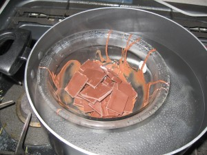 A glass bowl in hot water is a good way to melt chocolate if you can't get a