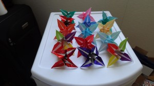 14 origami lilies of different colors and shades on a white table
