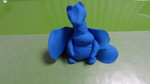 A blue clay dragon resting on its hind legs with thin wings but little detail