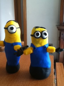 A slightly taller one-eyed yellow minion in blue coveralls and a slightly smaller two-eyed yellow minion in blue coveralls.