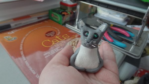 A gray cat with a white stomach, green bead eyes, and wire whiskers eyes me curiously from my palm.